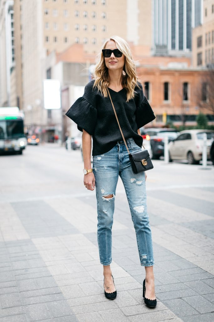 a girl with flowing top and mom jeans